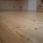 Borovicová dřevěná podlaha lakováná v interiéru.